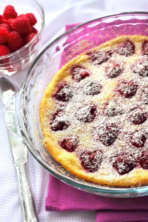 Flaugnarde with raspberries in glass baking form photo