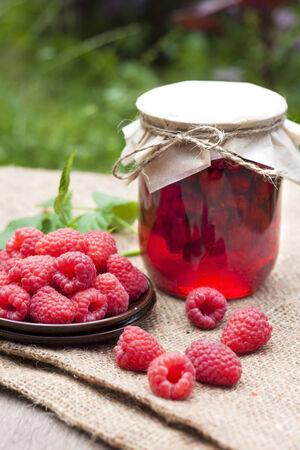 Raspberry preserve in glass jar and fresh raspberries on a plate photo