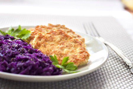 Chicken fritters and stewed red cabbage with caraway seeds. Shallow DOF