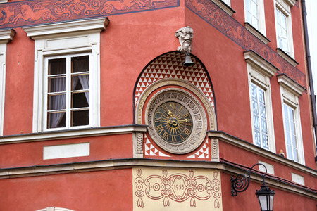 Old clock on the wall at the Market square in the old town of Warsaw, Poland