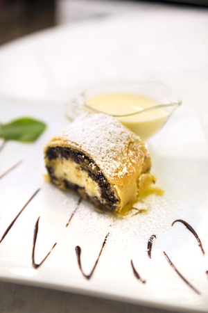 Poppy seeds and cream cheese strudel with custard and mint