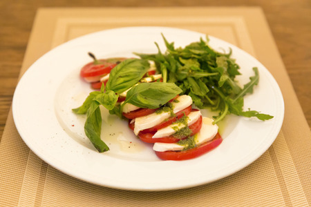 Caprese Salad - salad with tomato, mozzarella cheese and pesto sauce