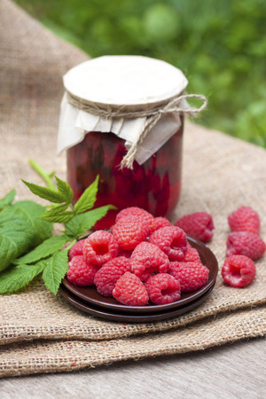 Raspberry preserve in glass jar and fresh raspberries on a plate Stock Photo - 38730557