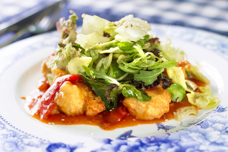 Salad with fried fish fillet, red pepper and salad mix