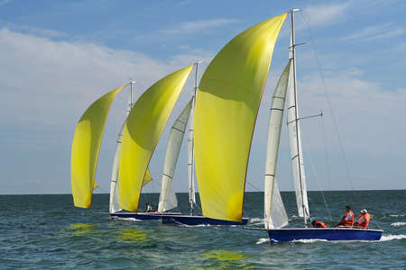 maneuver: Sports race of yachts. Three yachts compete with yellow sails. It is a rare very successful photo. Stock Photo