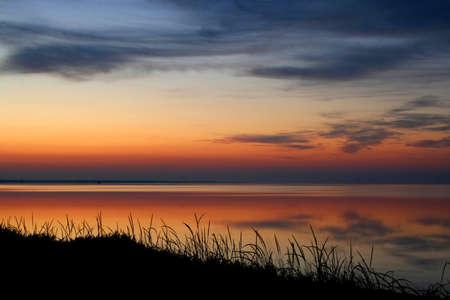 rise above: Early morning. The sun soon will rise above the sea and will illuminate clouds. In the quiet sea beautiful reflection. Pleasant colours. A quiet nature. Silhouettes of a grass on a coast