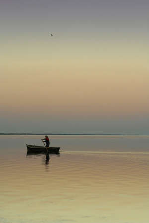 Lonely boat on silent water. Sunset. Beautiful reflection in water. One the man in a boat and one bird in the sky. The excellent quiet photo. photo