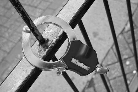 Handcuffs broken on a fencing.  A street of the large city. Someone has run away on freedom. Stock Photo - 577969