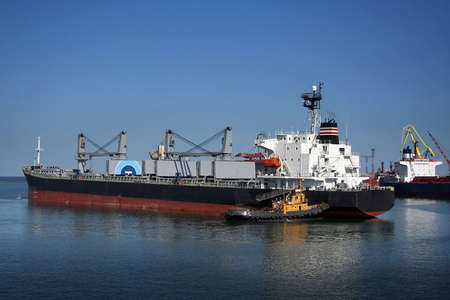 shove: In port tugboat helps the large courts to go in port. Such at it work. Stock Photo