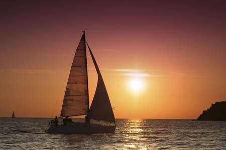 The yacht comes nearer to an island. The sails are filled by a wind. The day begins. photo