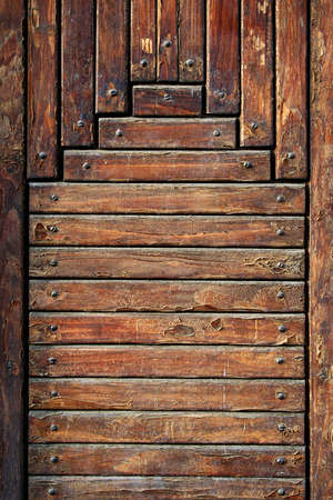 Old wooden boards fixed by screws. It is a fragment of a door. photo