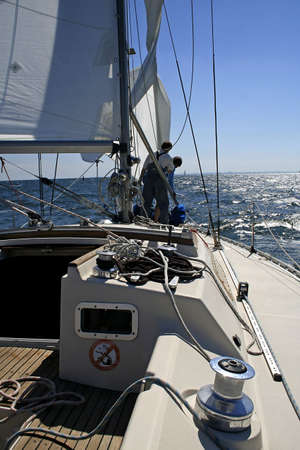 yachtsman: Two men work with sails. Onboard a beautiful yacht there is a rigging, cords and blocks.