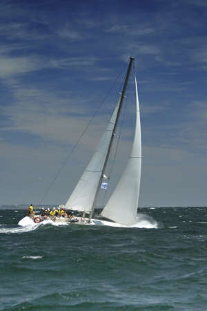 yachtsman: The large waves cover a sailing yacht. The team of a sailing yacht levels an inclination of a boat. Strong storm wind and large waves