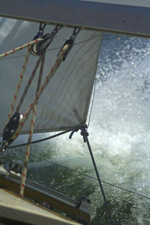 iatismo: The large waves cover a sailing yacht. Sails and rigging. Banco de Imagens