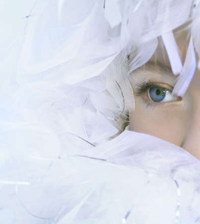 The angel has perfect light-blue eyes and white feathers Stock Photo