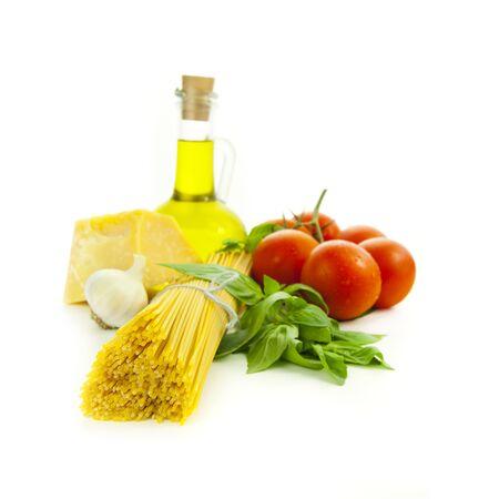 Ingredientes para cocinar italiano: albahaca, tomate, parmesano, ajo y espaguetis / aislados en blanco