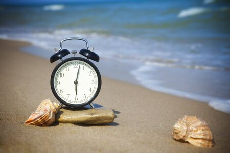 Time to relax! The sea is calling!  The alarm and seashells on the shore of the warm sea Stock Photo - 9925761