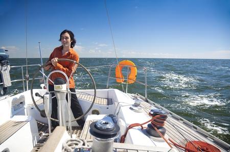 Junge skipper treibende Segelboot / Kapitän der Yacht