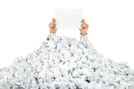 Person under crumpled pile of papers with hand holding a blank page  isolated on white Stock Photo