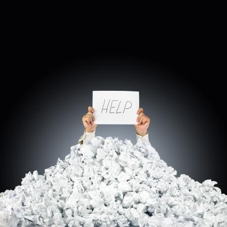 Persoon onder verfrommelde stapel papieren met de hand die een hulp teken