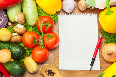 Organic Vegetables on Wooden Background and Notebook for Menu or Recipes Imagens