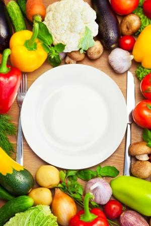 ナイフとフォークの垂直方向の組成を持つ白い平板まわりの新鮮な有機野菜