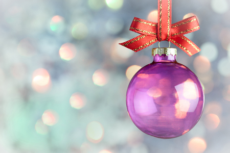 Christmas Decoration Beautiful magic bokeh with purple bauble and red ribbon over  light background Foto de archivo