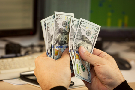 Hands count hundred dollar banknots on office background
