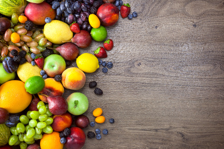 Different Organic Fruits  with  water drops on wooden table background - Healthy Eating Stockfoto