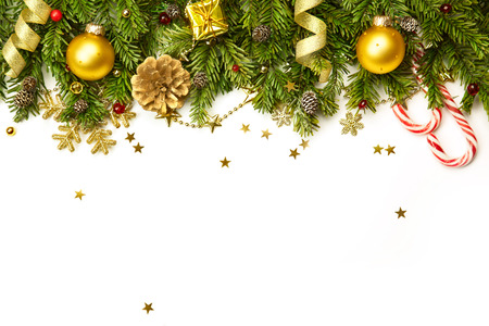 Christmas tree branches with golden baubles, stars, snowflakes isolated on white  -  horizontal border 写真素材