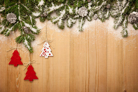 Christmas background with fresh firtree, decorative handmade trees and cones on wood with bright snow