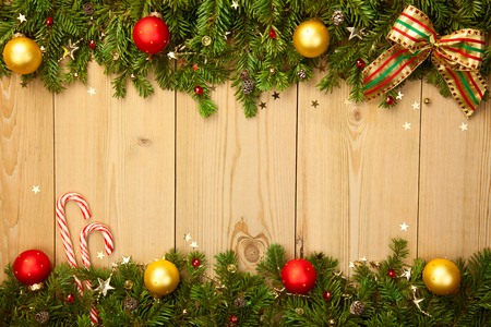 Christmas background with firtree, candies, baubles and stars on wood
