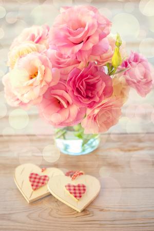 Liefde Vintage Achtergrond - Mooie Eustoma bloemen en twee harten, licht defocused Stockfoto