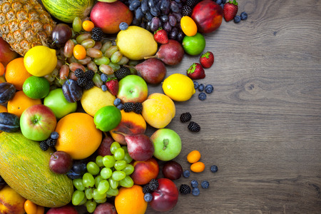 Mix of Fresh Fruits  on dark wooden table with copy space Stock Photo