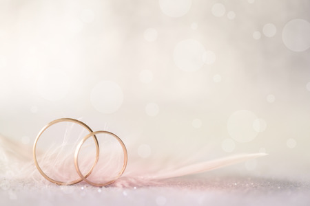 Two Golden Wedding Rings and  Feather - light soft background for marriage Archivio Fotografico