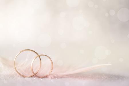 Due anelli di nozze d'oro e piume - sfondo morbida luce per il matrimonio Archivio Fotografico - 33465385