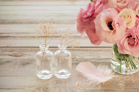 Still life with pink Eustoma flowers in a vase with fearher and two glass botles - vintage look