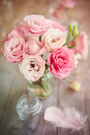 Bright romantic vertical background with roses feathers and bokeh Foto de archivo