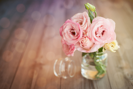 Colorful still life with roses in glass vase with bokeh background Foto de archivo