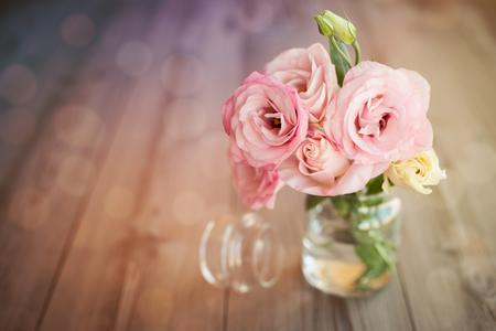 Kleurrijke stilleven met rozen in glazen vaas met bokeh achtergrond