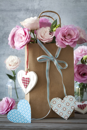 St. Valentines Day background with pink flowers, blue bow and paper and wooden hearts