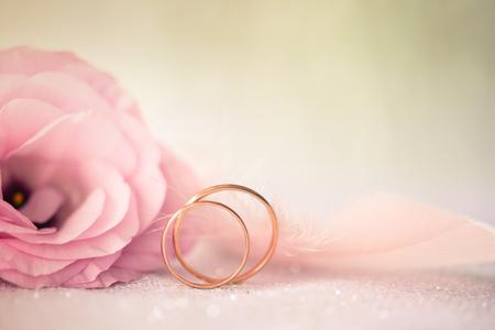 Achtergrond met gouden ringen en mooie roze bloem Stockfoto