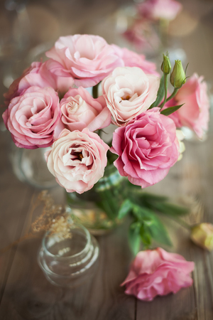 Romantic still life with fresh roses in vase with bokeh