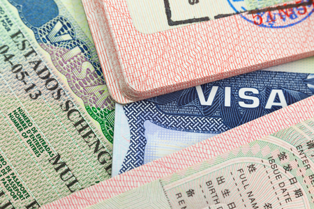 Chinese, USA and Shengen European visas in passports - adventure background