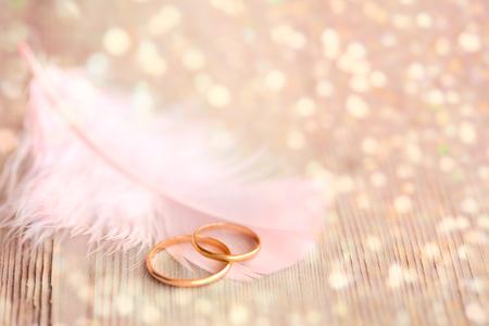 Achtergrond van het huwelijk met gouden ringen, roze veren en gouden magische lichten Stockfoto