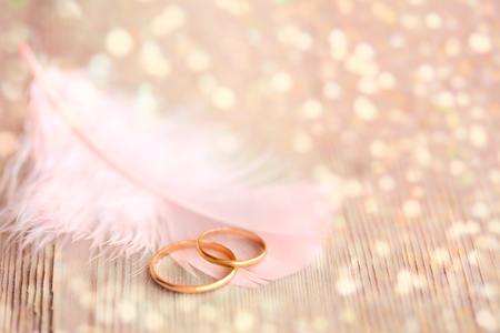 Wedding  Background with Gold Rings, pink feather and golden magical lights Stock Photo