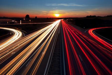 Snelheid Verkeerslicht paden op snelweg bij zonsondergang tijd, lange blootstelling, stedelijke achtergrond met zon en donkere hemel Stockfoto
