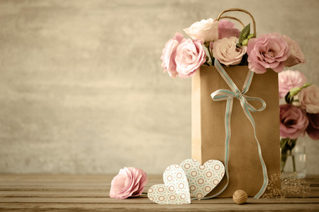 Love background with pink flowers, bow and paper handmade hearts, vintage toned 스톡 콘텐츠