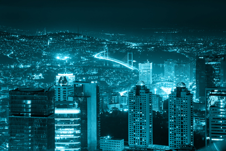 Night view of the illuminated city downtown, skyscrapers and bridge, blue toned, Istanbul, Turkey, Europe - Asia