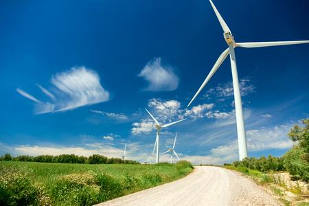 Generator van de wind Turbines in prachtige Real Landschap met gras en over de weg - concept van hernieuwbare energie, horizontaal Stockfoto